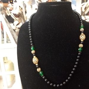 Black bead necklace with gold and green accents